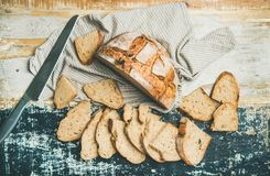 Sourdough wheat bread loaf. Flat-lay of freshly-baked sourdough wheat bread loaf halved and cut in slices over linen napkin and rustic table background, top view Royalty Free Stock Image