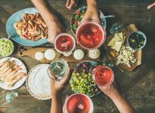Flat-lay of friends hands eating and drinking together Royalty Free Stock Photo