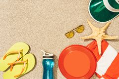 Flat lay with frisbee, cap, flip flops, sunglasses and water bottle arranged. On sand stock photo