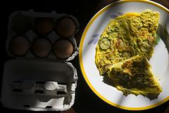Flat lay of frittata in constrast of light. Wedges of vegetarian frittata with near fresh eggs royalty free stock image