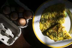 Flat lay of frittata in constrast of light. Wedges of vegetarian frittata with near fresh eggs royalty free stock photo