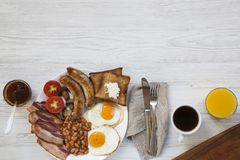 Flat lay of full english breakfast with fried eggs, sausages, bacon, beans and toasts on white wooden background. Top view. Copy s. Pace, text area Stock Image