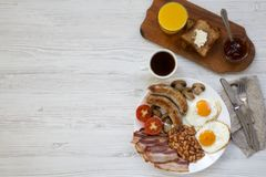 Flat lay, full english breakfast with fried eggs, sausages, bacon, beans and toasts. White wooden background. Top view. Copy space Stock Image