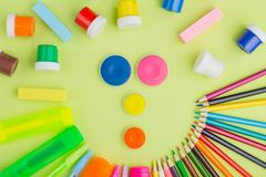 Flat lay Funny faces of stationery on a green background, multi-colored paints, pencils, markers, erasers. The concept stock images