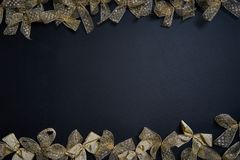Flat lay of golden gift bows on dark background. New year and christmas concept. royalty free stock images