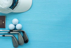 Flat lay : Golf clubs, golf balls, cap, passport. Golf clubs, golf balls, cap, passport on blue wooden table, with copy space Royalty Free Stock Photos