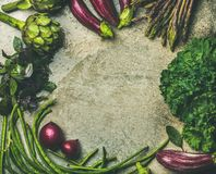 Flat-lay of fresh green and purple vegetables variety. Flat-lay of green and purple vegetables over concrete background, top view, copy space, food frame. Local Royalty Free Stock Photos