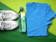 Flat lay on green sport mat background of sport t-shirt, pants, sneaker, fitness items, top view. Flat lay on green sport mat background of sport t-shirt, pants royalty free stock photo