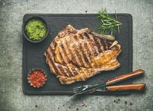 Grilled hot rib-eye beef steak on bone with chimichurri sauce. Flat-lay of grilled hot rib-eye beef steak on bone with chimichurri green sauce and hot red chili Royalty Free Stock Image