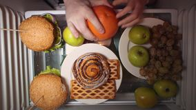 Flat lay of the hand take food at night with on the shelves of the refrigerator. stock footage