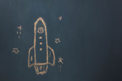 Flat lay Handmade drawing rocket ship launch / take off to the space with star on the blackboard by chalk board. Top view / Flat lay Handmade drawing rocket Royalty Free Stock Photo