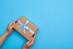 Flat lay of hands of female placing a present box on background Royalty Free Stock Photography