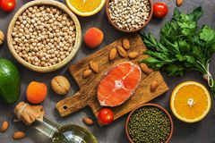 Flat lay healthy balanced raw food, salmon, legumes, vegetables, fruits, greens and nuts on a dark rustic background. View from. Above. The concept of healthy stock photo