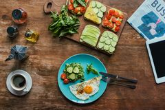 Flat lay with healthy breakfast on plate, cup of coffee, newspaper and tablet. On wooden tabletop royalty free stock photo