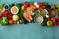 Flat lay healthy diet food cereals seeds fish vegetables fruits stone background top view. Flat lay healthy and diet food cereals, seeds, fish, vegetables and stock images