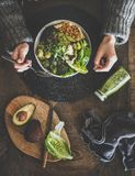 Flat-lay of healthy dinner vegetarian superbowl, smoothie and womans hands. Healthy dinner or lunch setting. Flat-lay of vegan superbowl or Buddha bowl with royalty free stock photography