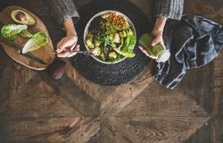 Flat-lay of healthy superbowl, smoothie and womans hands, copy space. Healthy dinner, lunch setting. Flat-lay of vegan superbowl or Buddha bowl with hummus royalty free stock images