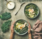 Healthy vegetarian quinoa egg breakfast bowl in female hands. Flat-lay of healthy vegetarianenergy boosting, breakfast bowl in female hands. Quinoa, kale, green Stock Images