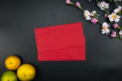 Flat lay holiday of Chinese new year red packet and of accessori. Es blossom on top and Lunar festival concept background, Other language means wealthy or rich stock photography