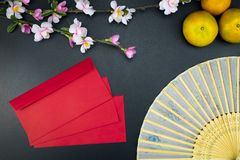 Flat lay holiday of Chinese new year red packet and of accessori. Es blossom on top and Lunar festival concept background, Other language means wealthy or rich royalty free stock photos