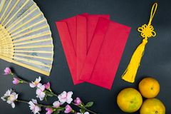 Flat lay holiday of Chinese new year red packet and of accessori. Es blossom on top and Lunar festival concept background, Other language means wealthy or rich stock photo