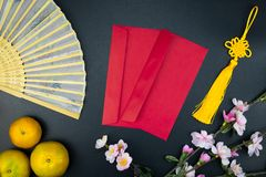 Flat lay holiday of Chinese new year red packet and of accessori. Es blossom on top and Lunar festival concept background, Other language means wealthy or rich royalty free stock images