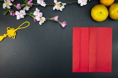 Flat lay holiday of Chinese new year red packet and of accessori. Es blossom on top and Lunar festival concept background, Other language means wealthy or rich royalty free stock image