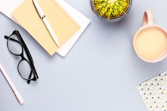 Flat lay home office desk. Female workspace with note book, eyeglasses, tea mug, diary, plant. Copy space. Top view stock photography
