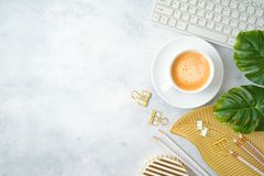 Free Flat Lay Home Office Feminine Table With Coffee Cup, Golden Accessories, Computer Keyboard And Tropical Leaves On Grey Background Stock Photography - 151875682