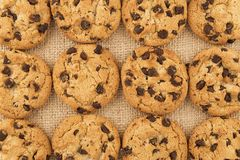 Flat lay of homemade chocolate chip cookies on burlap. royalty free stock images