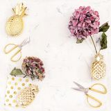 Flat lay hortensia flowers vintage scissors. Flat lay with hortensia flowers and vintage scissors on white marble background Royalty Free Stock Photo