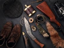 Flat lay with hunting accessoties over the grey background: old. Flat lay with hunting ammunition over the grey background: old boots, hat, rifle, knife, rope royalty free stock images