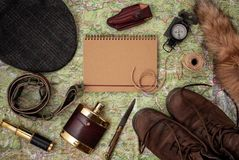 Flat lay with hunting ammunition over the map as background: old. Boots, hat, knife, rope, belt, fox tail. Top view stock photo