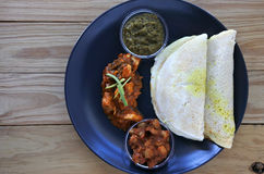 Flat lay of Indian food,  Chicken Curry served with Masala Dosa Royalty Free Stock Image