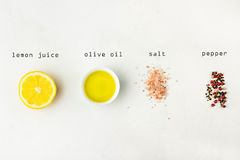 Flat lay of ingredients for vinaigrette sauce. Lemon, olive oil, Himalayan salt red black white pepper on white stone background. Typed lettering. Poster, menu Royalty Free Stock Photos