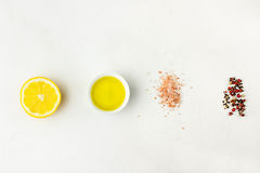 Flat lay of ingredients for vinaigrette sauce. Lemon, olive oil, Himalayan salt red black white pepper on white stone background. royalty free stock images