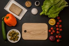 Flat lay. Italian food. Brown wooden cutting board surrounded by plant based ingredients for vegan greek salad. Copy space. Flat lay, top view. Italian food royalty free stock photography