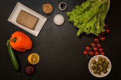 Flat lay. Italian food. Plant based ingredients for vegan greek salad on black background. Copy space royalty free stock photography