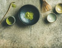 Japanese tools for brewing matcha green tea, grey concrete background. Flat-lay of Japanese tools for brewing matcha green tea. Matcha powder in tin can stock photography