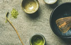 Japanese tools for brewing matcha tea, grey concrete background. Flat-lay of Japanese tools for brewing matcha green tea. Matcha powder in tin can, Chashaku royalty free stock photos