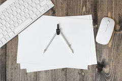 Flat lay of keyboard, pc mouse, compass and paper on wooden surface. Workplace of architect, constructor, designer in top view. Start a new project Royalty Free Stock Images