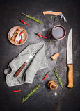 Flat lay with kitchen cooking tools, glass of red wine, herbs and spices on dark rustic background. Top view Royalty Free Stock Photo