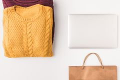 Flat lay with knitted sweaters, laptop and shopping bag,. Isolated on white stock photography