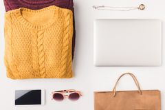 Flat lay with knitted sweaters, sunglasses, pendant, laptop, smartphone and shopping bag,. Isolated on white stock photo