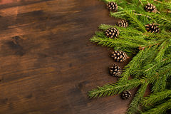 Flat lay: larch and fir branches and pine cones on the wood desk. Flat lay chrismas rpattern, larch and fir branches and pine cones on the wood desk. emty space Royalty Free Stock Photography