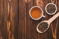 Flat lay layout with herbal tea. White cup with hot tea. A wooden spoon with dried tea leaves on wooden background. View from above stock photos