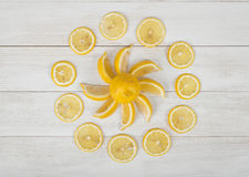 Flat lay of lemon pieces laid out into the sun shape and well decorated slices around it. Stock Photo