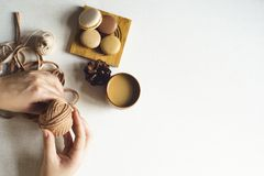 Flat lay lifestyle craft. Homemade colorful macarons on the wooden plate on the white background. Female hand is holding yarn. Flat lay with copy space for text royalty free stock photography
