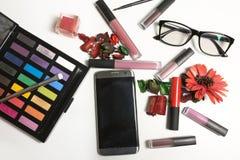 Flat lay of  lipstick, lip gloss, glasses and mobile phone over. Flat lay of  lipstick, lip gloss, glasses and mobile phone on a white background Royalty Free Stock Photography