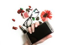 Flat lay of  lipstick, lip gloss, glasses and mobile phone in wo. Flat lay of  lipstick, lip gloss, glasses and mobile phone in female hand over a white Stock Photos